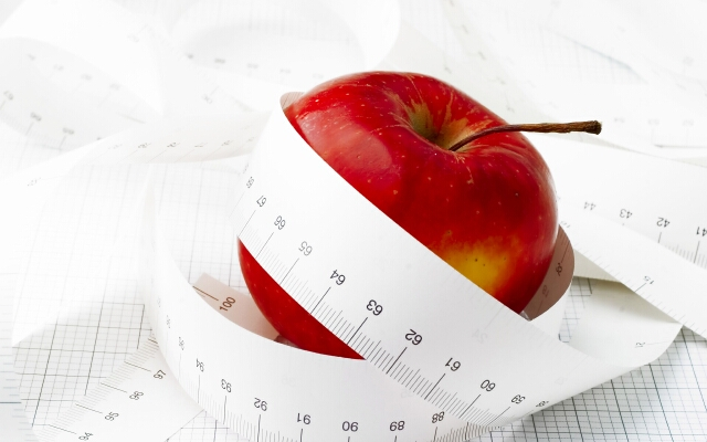 Measuring tape and red apple. Symbolic.