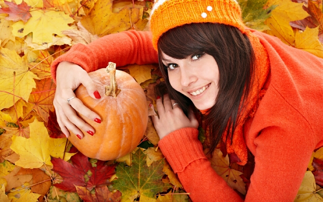Girl with  pumpkin on autumn leaves.