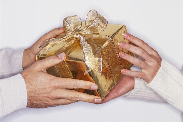 Hands Exchanging Wrapped Gift
